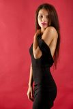 Sexy brunette woman in black dress. Isolated on red background Royalty Free Stock Image