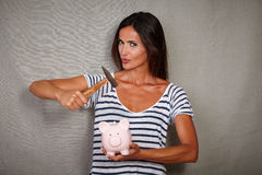 Sexy brunette woman breaking a piggy bank Royalty Free Stock Images