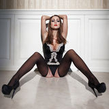 Sexy brunette woman in corset sit on floor at night Royalty Free Stock Images