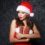 Sexy brunette woman embrace Christmas gift Royalty Free Stock Images