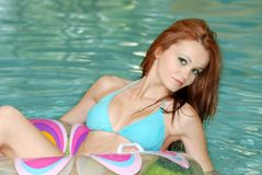 brunette woman floating in swimming pool Stock Images
