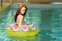 Sexy brunette woman in a floating water toy Royalty Free Stock Images
