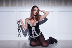 Sexy brunette woman holding handcuffs Royalty Free Stock Image