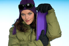 Sexy brunette woman holding purple skis Stock Photo