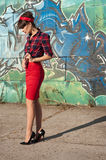 Sexy brunette woman. Sexy hot brunette pinup woman model wearing red headband, checked shirt and skirt, black high heels, posing, standing against green and blue Stock Photography