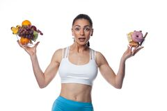 Sexy Brunette Woman In Fitness Suit Eating Fruits And Candies Royalty Free Stock Photography