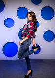 Sexy brunette woman in jeans and high heels posing in studio Royalty Free Stock Photos