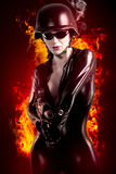 Sexy brunette woman in latex jumpsuit with heavy gun and helmet. Over fire background, dark Royalty Free Stock Photography