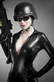 Sexy brunette woman in latex jumpsuit with heavy gun and helmet. Black Royalty Free Stock Photo