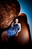 Sexy brunette woman leaning against rusty pipe Stock Photo