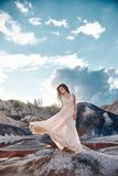 Sexy brunette Woman in long dress standing in the wind on a back Stock Photo