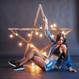 brunette woman in nice jeans in the studio. Wooden star with lights on a black background Stock Image