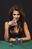 Sexy brunette woman with poker cards. On black background Royalty Free Stock Photos