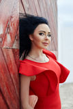 brunette woman in a red dress is standing near the red gate Royalty Free Stock Photo