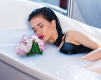 Sexy brunette woman relaxing in a hot bath with flowers. Closeup view of Sexy brunette woman lying on one side in a hot bath with flowers. she is wearing black Stock Images