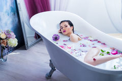 Sexy brunette woman relaxing in a hot bath with flowers. Sexy brunette woman lying on one side in a hot bath with flowers. she is wearing black sexual lingerie Royalty Free Stock Photography