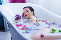 Sexy brunette woman relaxing in a hot bath with flowers. Sexy brunette woman lying on one side in a hot bath with flowers. she is wearing black sexual lingerie Royalty Free Stock Image
