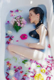 Sexy brunette woman relaxing in a hot bath with flowers. Sexy brunette woman lying on one side in a hot bath with flowers. she is wearing black sexual lingerie Stock Image