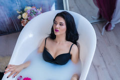 Sexy brunette woman relaxing in hot milk bath with flowers Royalty Free Stock Photos