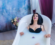 Sexy brunette woman relaxing in hot milk bath with flowers Royalty Free Stock Images