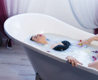 Sexy brunette woman relaxing in hot milk bath with flowers. Woman in bath. Sexy brunette woman relaxing in hot milk bathtube with flowers. she is wearing black Stock Images