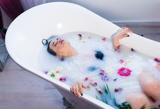 Sexy brunette woman relaxing in hot milk bath with flowers. Woman in bath. Sexy brunette woman relaxing in hot milk bathtube with flowers. she is wearing black Stock Photos
