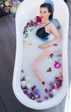 Sexy brunette woman relaxing in hot milk bath with flowers. She is wearing black sexual lingerie and looking at camera Royalty Free Stock Images