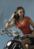 Sexy brunette woman seated on motorcycle Stock Photo