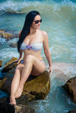 Sexy brunette woman sits on rocks at the seashor Royalty Free Stock Photo
