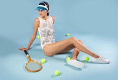 Sexy brunette woman sitting near tennis racquet and balls Stock Image