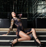 Sexy brunette woman sitting on stairs in nightclub Royalty Free Stock Image