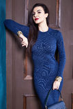 Sexy brunette woman skinny business style dress blue knit Royalty Free Stock Photos