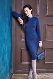 Sexy brunette woman skinny business style dress blue knit Stock Photography