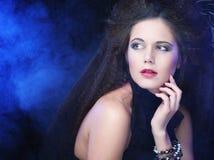 Brunette woman in smoke. RPortrait of a beautiful and brunette woman in smoke royalty free stock photos