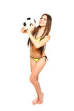 Sexy brunette woman in a swimsuit posing with soccer ball on a w Stock Images