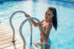 Sexy brunette woman in swimsuit relaxing in swimming pool Royalty Free Stock Images