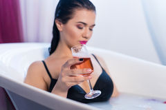 Sexy brunette woman taking a hot bath with flowers. Sexy brunette woman relaxing in a hot bath with flowers and champagne . she is wearing black sexual lingerie Royalty Free Stock Image
