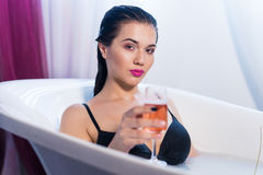 Sexy brunette woman taking a hot bath with flowers. Sexy brunette woman relaxing in a hot bath with flowers and champagne . she is wearing black sexual lingerie Stock Photography
