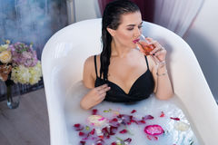 Sexy brunette woman taking a hot bath with flowers. Sexy brunette woman relaxing in a hot bath with flowers and drinking champagne . she is wearing black sexual Stock Photography