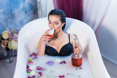 Sexy brunette woman taking a hot bath with flowers. Sexy brunette woman relaxing in a hot bath with flowers and drinking champagne . she is wearing black sexual Royalty Free Stock Images