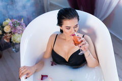 Sexy brunette woman taking a hot bath with flowers. Sexy brunette woman relaxing in a hot bath with flowers and drinking champagne . she is wearing black sexual Stock Image