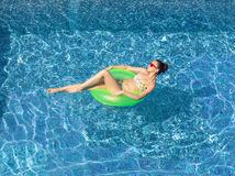 Sexy brunette woman tanning on inflatable circle in swimming poo Royalty Free Stock Images