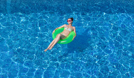 Sexy brunette woman tanning on inflatable circle in swimming poo. One beautiful woman on green inflatable torus in swimming pool Royalty Free Stock Photography