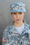 Sexy brunette woman with USA flag on army uniform posing at gray wall Royalty Free Stock Images