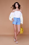 Sexy brunette woman wear short blue cotton short and silk summer. Collection blouse perfect body shape diet skin tan hold accessory bag glamour model fashion Stock Photos