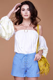 Sexy brunette woman wear short blue cotton short and silk summer. Collection blouse perfect body shape diet skin tan hold accessory bag glamour model fashion Stock Photo