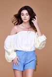 Sexy brunette woman wear short blue cotton short and silk summer. Collection blouse perfect body shape diet skin tan hold accessory bag glamour model fashion Royalty Free Stock Images