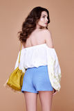 Sexy brunette woman wear short blue cotton short and silk summer. Collection blouse perfect body shape diet skin tan hold accessory bag glamour model fashion Stock Image