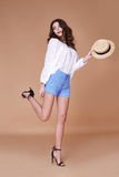 Sexy brunette woman wear short blue cotton short and silk summer. Collection blouse perfect body shape diet skin tan hold accessory hat glamour model fashion Royalty Free Stock Images