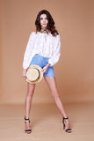 Sexy brunette woman wear short blue cotton short and silk summer. Collection blouse perfect body shape diet skin tan hold accessory hat glamour model fashion Royalty Free Stock Photos